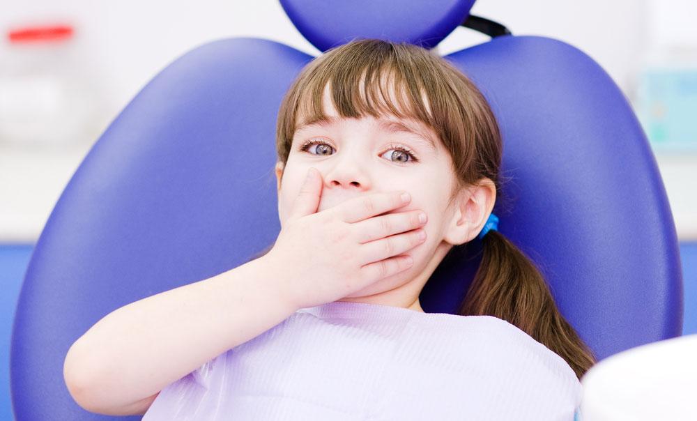 Liten tjej som har tandläkareskräck